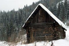 Oude die logboekhut bij de voet van een heuvel met de winterbos wordt overwoekerd royalty-vrije stock afbeelding