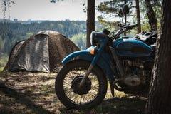 Oude die motorfiets met sidecar op het kamperen wordt geparkeerd royalty-vrije stock fotografie
