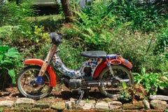 Oude die motorfiets naast een bospark in Thailand wordt geparkeerd stock foto