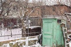 Oude die omheining met sneeuw voor een oud huis wordt behandeld, de winter ijzige scène royalty-vrije stock afbeeldingen