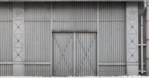 Oude die opslag de bouwmuur van geribbeld staal wordt gemaakt stock afbeelding