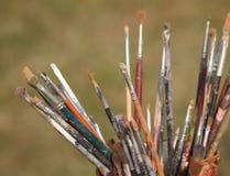 Oude die reeks borstels door een schilder in het schilderen van workshop worden gebruikt Stock Foto's