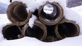 Oude die rioolbuizen met sneeuw worden behandeld Stock Afbeeldingen