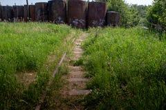 Oude die spoorweg met gras wordt overwoekerd royalty-vrije stock afbeelding