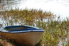 Oude die vissersboot met een hangslot en een ketting in het riet wordt gesloten royalty-vrije stock afbeelding