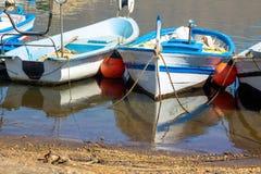 Oude die vissersboten aan de kust met kalme overzees en bezinning worden gebonden Royalty-vrije Stock Afbeelding
