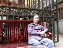 Oude die vrouw als voorzitter wordt gezeten om in gemeenschap te rusten Royalty-vrije Stock Foto
