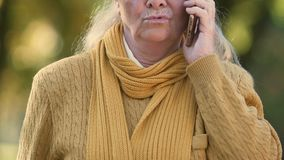 Oude die vrouw door slecht nieuws van telefoon, ontevreden met mobiele verbinding wordt verstoord stock footage