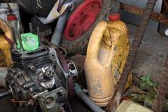 Oude Dieselmotor met de Lege Fles van de Machineolie en Vuil Wiel - Slordige Garage stock fotografie