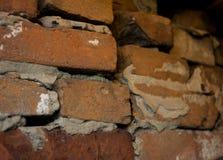 Oude donkere bruine en rode bakstenen muur met de achtergrond van de cementdunne modder, oud metselwerk Stock Afbeeldingen