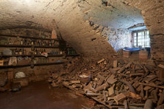 Oude, donkere kelderverdieping met houten stapelbinnenland Stock Foto