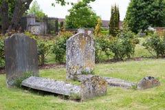 Oude doorstane graven in kerkhof Stock Afbeelding