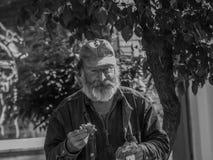 Oude, droevige dakloze persoon die een sandwitch eten royalty-vrije stock afbeelding
