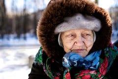 Oude droevige grootmoeder die in een sjaal wordt verpakt die de afstand onderzoeken stock foto's