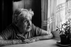 Oude eenzame vrouwenzitting dichtbij het venster in zijn huis royalty-vrije stock foto