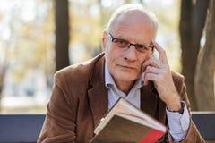 Oude elegante mens die een boek buiten lezen Stock Afbeelding