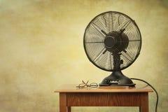 Oude elektrische ventilator op lijst met retro blik Stock Foto's
