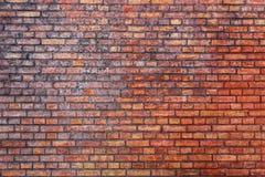 Oude en doorstane grungy rode bakstenen muur duidelijk door de lange blootstelling aan de elementen als achtergrond van de opperv Stock Afbeelding