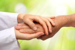 Oude en jonge hand, verpleegster arts Stock Foto