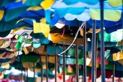 Oude en open scheurparaplu om de zonneschijn voor Toeristen bij het Bangsaen-Strand Chonburi Thailand te beschermen stock foto