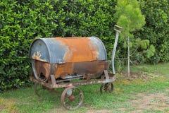 Oude en roestige metaalkruiwagen met oud vat op het Royalty-vrije Stock Afbeelding