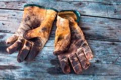 Oude en vuile werkende handschoenen over houten lijst, handschoenen voor elke vinger stock afbeeldingen