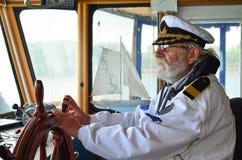 Oude ervaren kapitein in navigatiecabine stock afbeelding