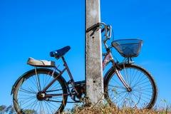 Oude fiets die op de elektrische pool en de blauwe hemel leunen Royalty-vrije Stock Afbeeldingen