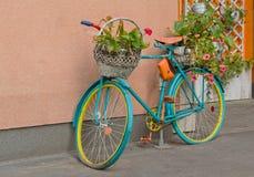 Oude fiets met bloemen en een mand door de muur Stock Foto's