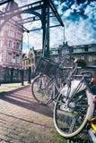 Oude fiets op brug. Cityscape van Amsterdam Stock Foto
