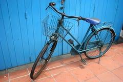 Oude fiets tegen blauwe deur Royalty-vrije Stock Afbeeldingen