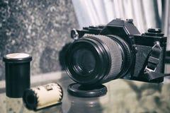Oude filmcamera en een broodje van film fotografisch materiaal, selectieve nadruk, zwart-wit korreleffect stock fotografie