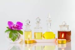Oude flessen aromatische oliën met kaarsen, bloemen, blad, handdoek op glanzende witte lijst Stock Fotografie