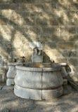 Oude fontein die zich in de bomenschaduwen bevinden in de ruïnes Royalty-vrije Stock Foto
