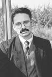 Oude foto van de mens in kostuum met een snor en glazen op trai stock afbeeldingen