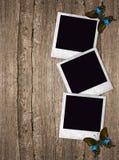 Oude fotokaders met vlinders over houten achtergrond Royalty-vrije Stock Afbeeldingen