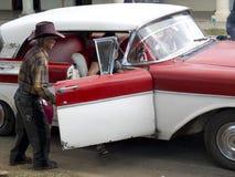 Oude gaucho die een deur van een uitstekende auto openen Stock Afbeeldingen