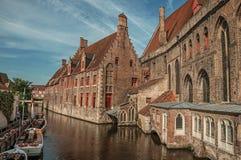 Oude gebouwen op de kanaalbank, de boten en de zonnige blauwe hemel in Brugge Stock Afbeelding