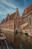 Oude gebouwen op de kanaalbank, de boten en de zonnige blauwe hemel in Brugge Stock Fotografie