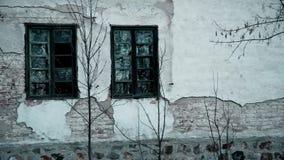 Oude gebroken vensters en een muur op een verlaten huis in de berg stock videobeelden