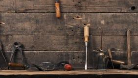 Oude gebruikte timmermanshulpmiddelen op hout stock foto