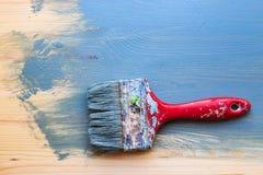 Oude gebruikte verfborstel op gedeeltelijke verf houten achtergrond horizonta stock afbeelding
