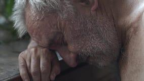 Oude gedeprimeerde mens bij de lijst stock videobeelden