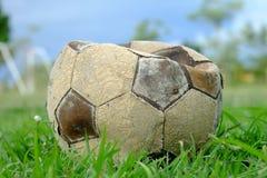 Oude gelaten leeglopen voetbalbal, oude gelaten leeglopen voetbal op het groene gras Stock Afbeelding
