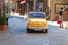 Oude gele auto Fiat 500 in San Marino, Italië Stock Afbeelding