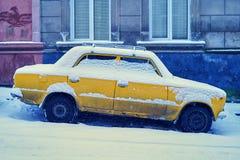 Oude gele die auto met sneeuw wordt behandeld op een sneeuw hellende straat in de winterstad wordt geparkeerd royalty-vrije stock fotografie