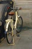 Oude gele fiets leerzetel met schokbrekers en wiel Stock Fotografie
