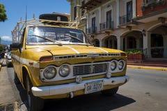 Oude gele oogstvrachtwagen die voor een koloniaal gebouw in de stad van Granada in Nicaragua wordt geparkeerd Royalty-vrije Stock Foto's