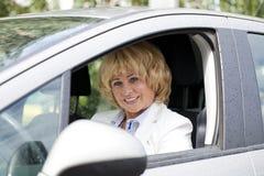 Oude gelukkige bejaarde bestuurdersvrouw 55-60 jaar in jasje die a.c. drijven Stock Afbeeldingen