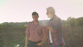 Oude gelukkige gecultiveerd gebied tonen aan zijn zoon en landbouwer die, papa die zijn erfgenaam over landbouw onderwijzen, lens stock video